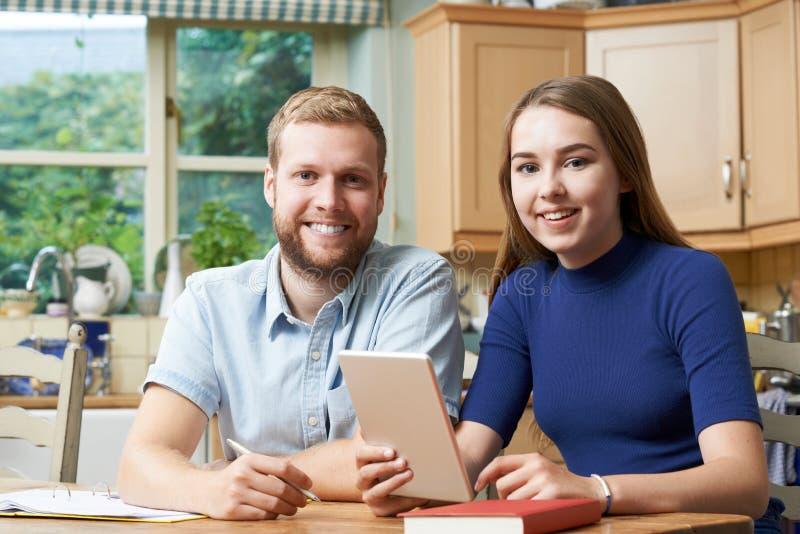Tutor home masculino Helping Teenage Girl com estudos fotos de stock royalty free