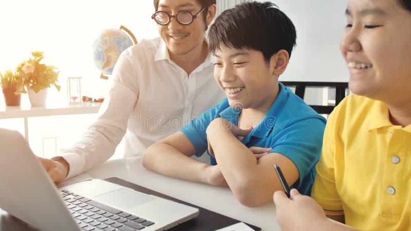 Tutor i bambini della stanza nella classe che impara sul computer portatile fotografie stock