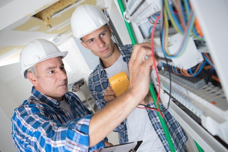 Tutor instructing trainee electrician royalty free stock images