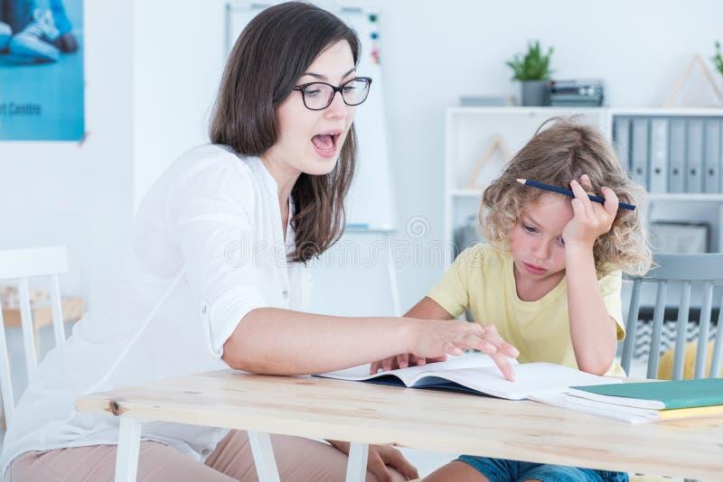Tutor o ensino uma criança autística de uma língua estrangeira em um escritório imagem de stock
