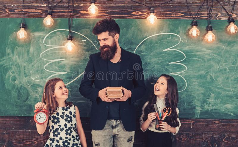 Tutor and pupils smile with school supplies. Happy teacher and schoolgirls at chalkboard. Bearded man and small girls at royalty free stock images