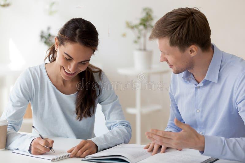 Tutor que ajuda o estudante fêmea que faz anotações com trabalho de pesquisa imagem de stock royalty free