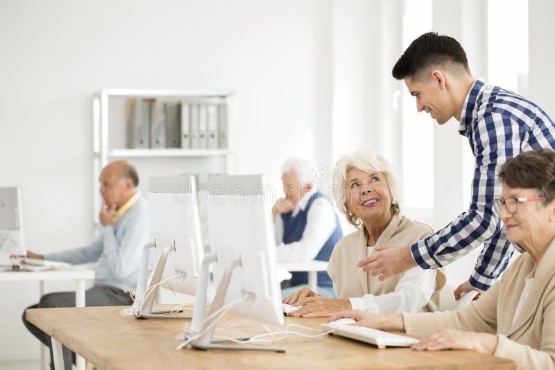 Tutor som förklarar uppgift till pensionären fotografering för bildbyråer