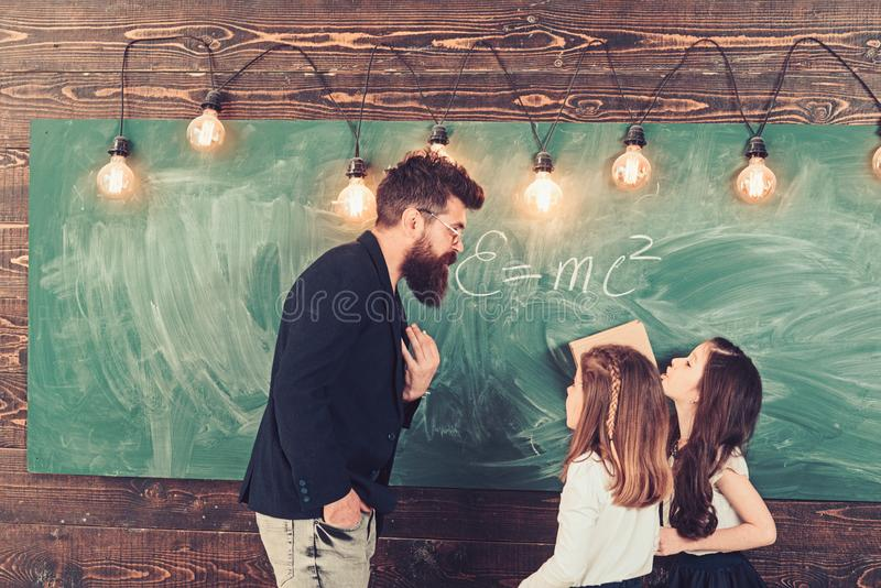 Tutor teach children students in classroom. Teacher write with chalk on chalkboard. Little girls listen to bearded man royalty free stock photography
