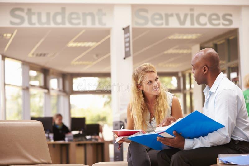 Tutor To Discuss Work de Having Meeting With da estudante universitário fotografia de stock