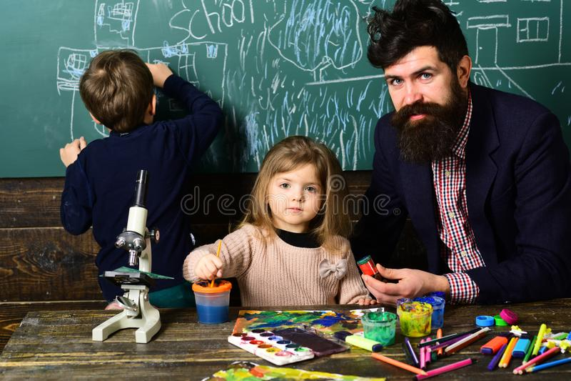 Tutor will require child to learn specific skill before advancing to level. University studying friends reading a books. In classroom. Help with homework is stock photo