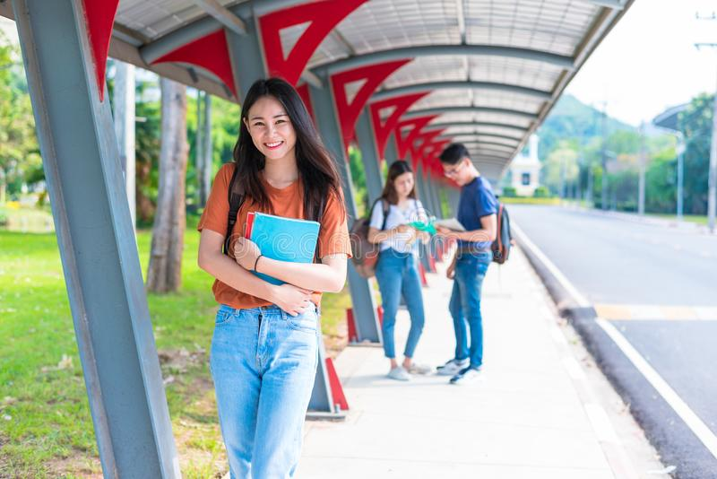 Tutoria dos estudantes da faculdade e livro de leitura asiáticos novos no walkwa imagens de stock