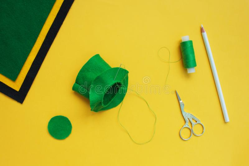 Tutorial how to sew felt leprechaun hat for St. Patrick`s day. Concept of DIY sewing art project. Step by step photo instruction. Top view, copy space. Step 4 stock image