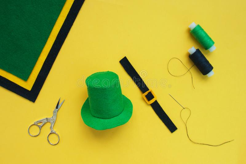 Tutorial how to sew felt leprechaun hat for St. Patrick`s day. Concept of DIY sewing art project. Step by step photo instruction. Top view. Step 6 in a buckle royalty free stock photography