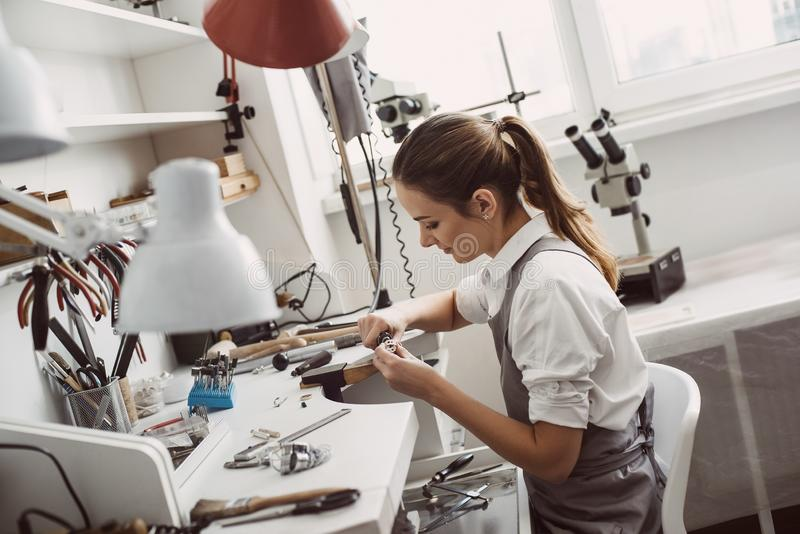 Tutti circa lavoro Ritratto alto vicino di un gioielliere femminile che lavora ad un anello al suo banco da lavoro Processo di fa fotografie stock libere da diritti