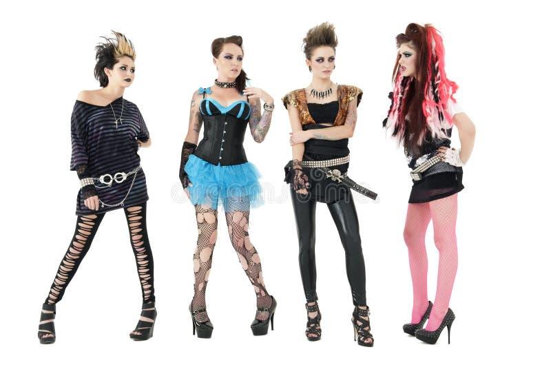 Tutti i membri di banda rock femminili che posano sopra il fondo bianco immagine stock