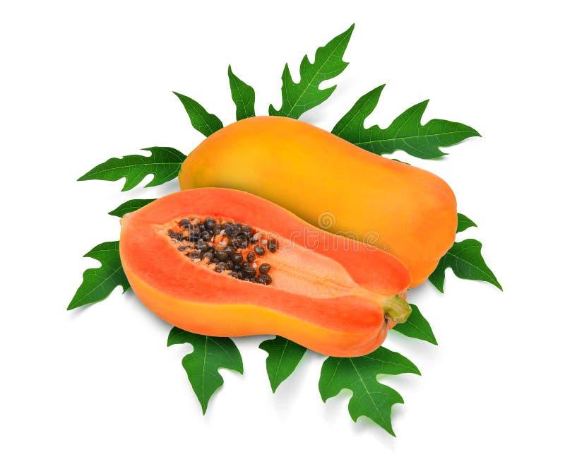 Tutto e metà della papaia matura con la foglia verde della papaia isolata immagine stock