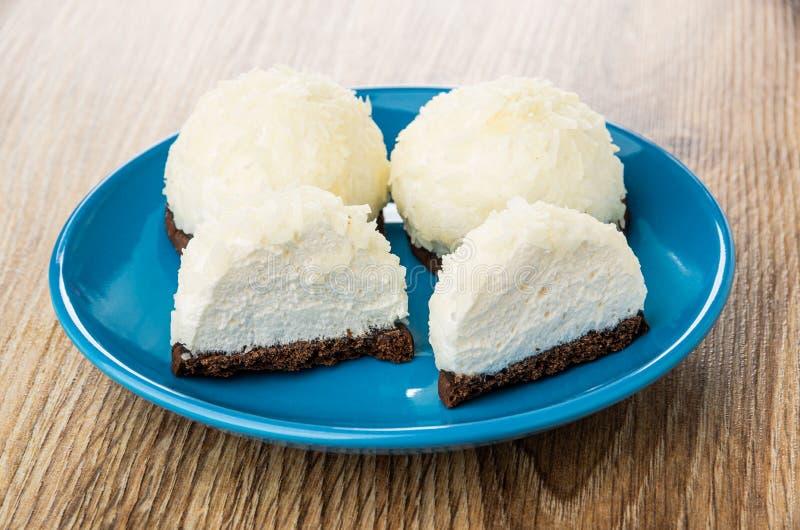 Tutto e metà delle caramelle gommosa e molle con la noce di cocco che si rade in piattino sulla tavola immagini stock libere da diritti