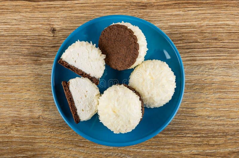 Tutto e metà delle caramelle gommosa e molle con la noce di cocco che si rade in piattino sulla tavola Vista superiore immagine stock libera da diritti