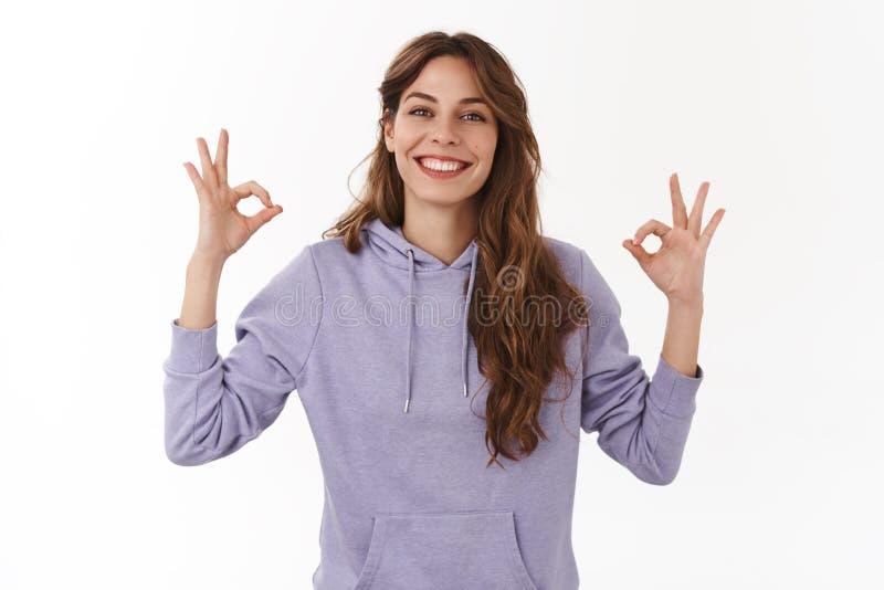 Tutto okay ha ottenuto sotto controllo I giovani rilassati allegri hanno assicurato il gesto eccellente sorridente della ragazza  fotografia stock