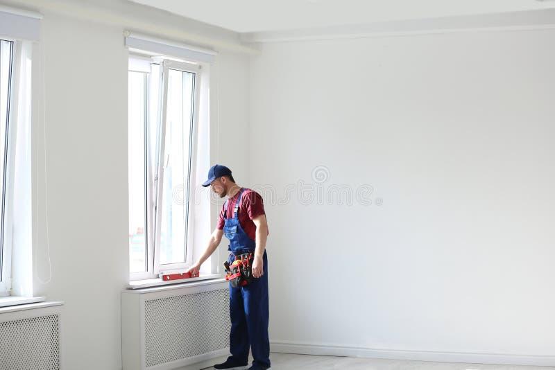 Tuttofare in uniforme che funziona con il livello della costruzione all'interno Strumenti professionali della costruzione immagine stock