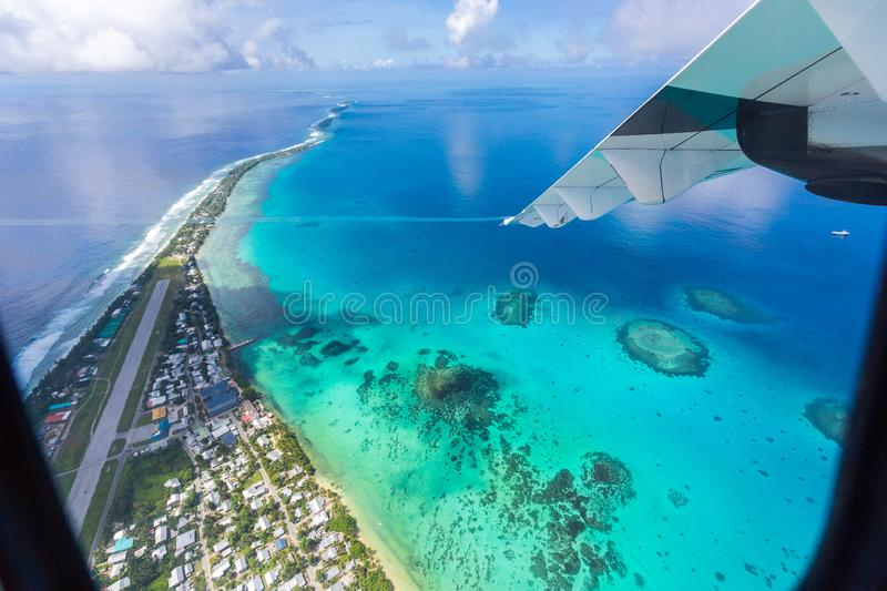 Tuvalu island azure turquoise blue lagoon under the wing of an airplane, aerial view. Polynesia, Oceania. royalty free stock images