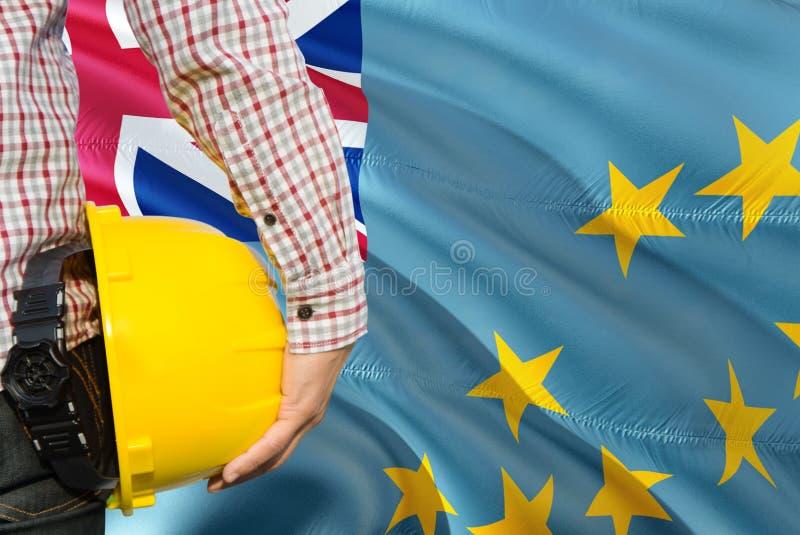 Tuvaluan inżynier trzyma żółtego zbawczego hełm z machać Tuvalu chorągwianego tło Budowy i budynku poj?cie obraz royalty free