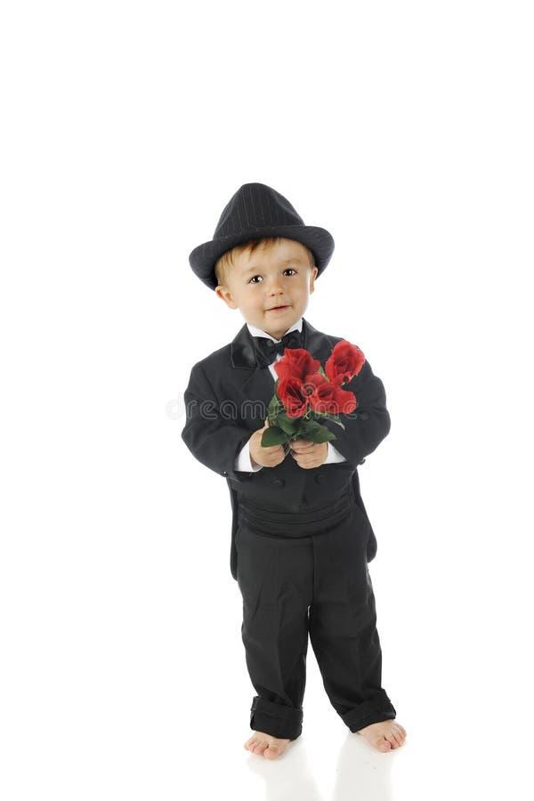 Tuxed litet barn med rosor royaltyfria foton