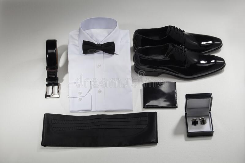 Tuxedo. Arm buttons, white shirt, black bow tie, belt, classic shoes and wallet. Isolated on white background royalty free stock photography