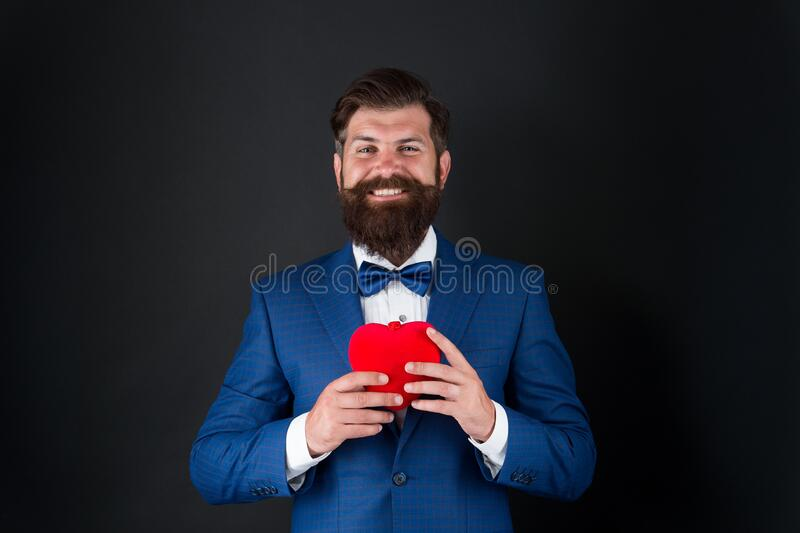 Tuxedo man with red heart. love and romance. ready for date. brutal bearded hipster in formal outfit. confident and royalty free stock images