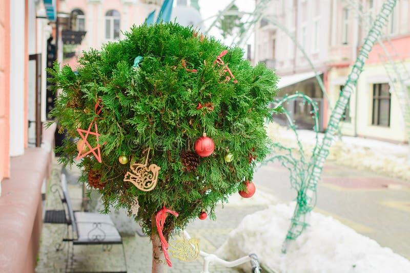 Tuya en la forma de una bola se adorna como vínculo del Año Nuevo con las bolas y los juguetes rojos del árbol en la calle y la c fotos de archivo