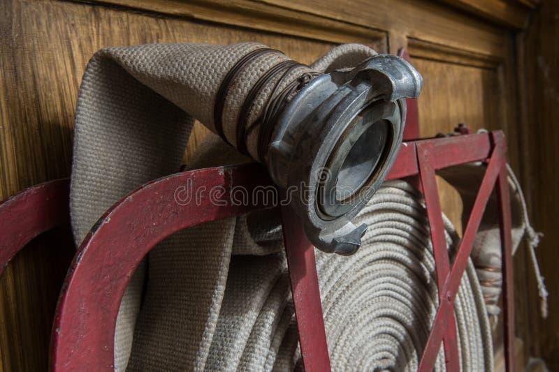 Tuyau d'incendie tordu sur le bouclier du feu photographie stock libre de droits