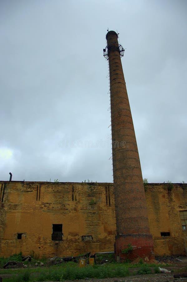 Tuyau de la vieille usine sur le fond d'un immeuble de brique délabré Paysage images libres de droits