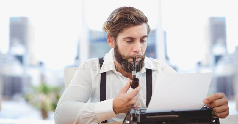 Tuyau de tabagisme hippie d'homme d'affaires tout en à l'aide de la machine à écrire photographie stock