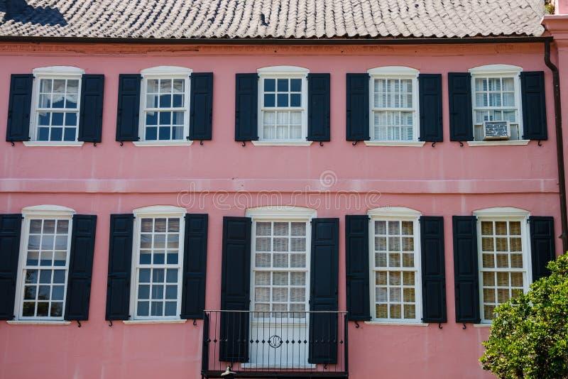 Tuyau et balcon noirs de volets sur le stuc rose image libre de droits