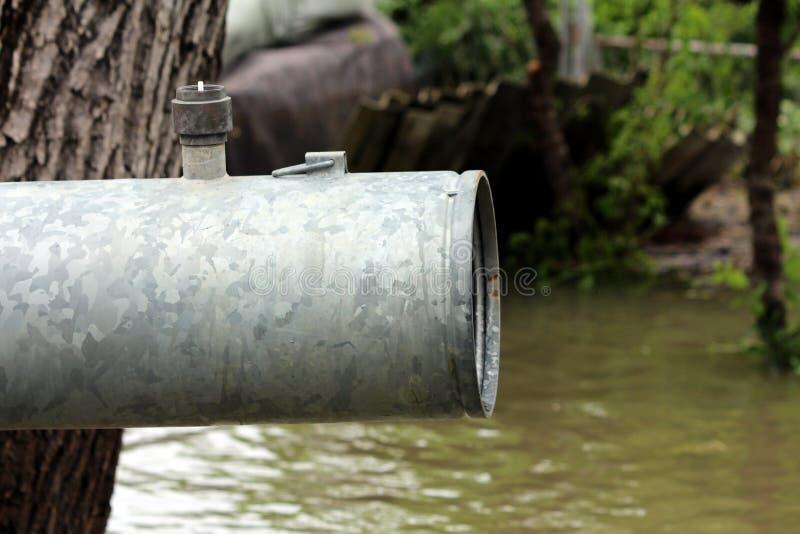 Tuyau fort en métal de grand diamètre avec la vanne de régulation absente sur le dessus à côté du vieil arbre employé pour pomper photographie stock
