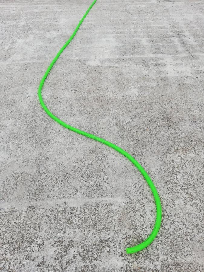 Tuyau vert d'irrigation sur une dalle en béton renforcé images stock