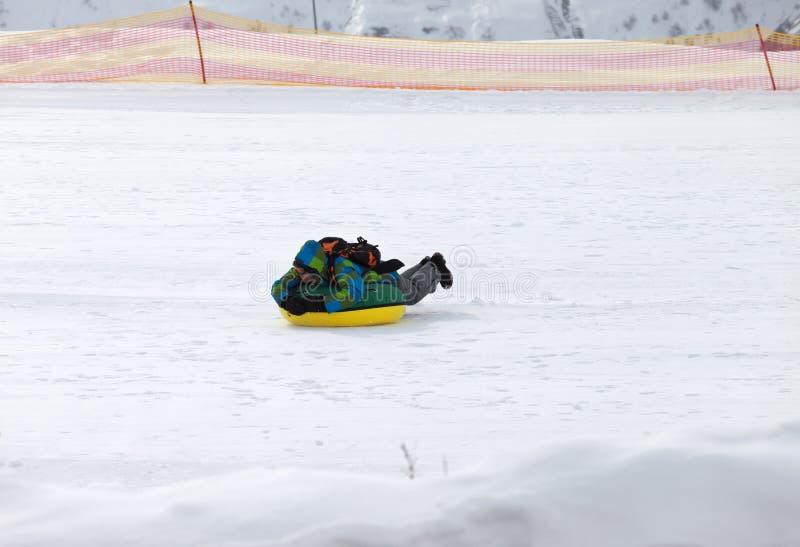 Tuyauterie de neige sur la station de sports d'hiver au jour ensoleillé en montagnes neigeuses photographie stock libre de droits