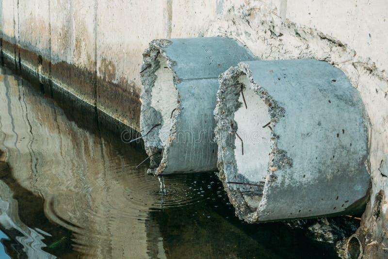 Tuyaux concrets de drainage ou de système d'égouts, eau sale et pollution d'environnement photographie stock libre de droits
