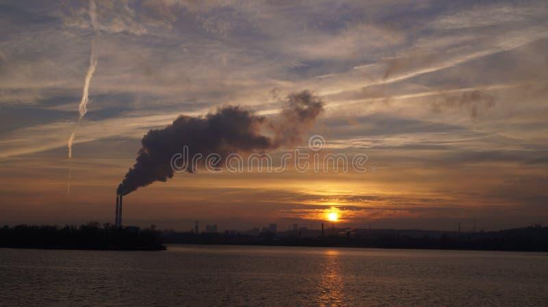 Tuyaux de rivière de ciel de fumée de coucher du soleil image stock