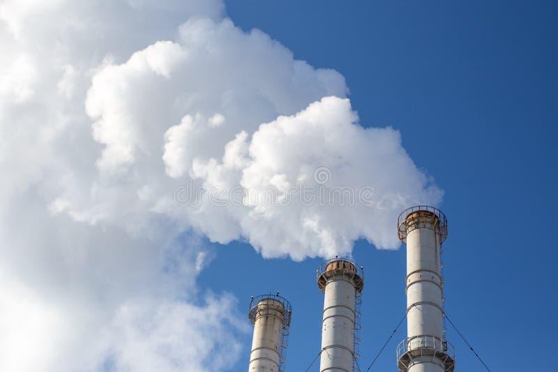Tuyaux de tabagisme faisant des nuages sur le fond de ciel bleu Contamination d'air de bioxyde pollution environnementale écologi photographie stock libre de droits