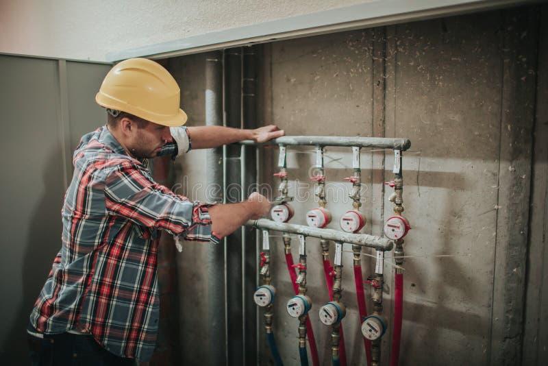 Tuyaux en plastique soudés par plombier Le travailleur avec le casque de construction se tient sur le site cbuilding et ne sait p photographie stock