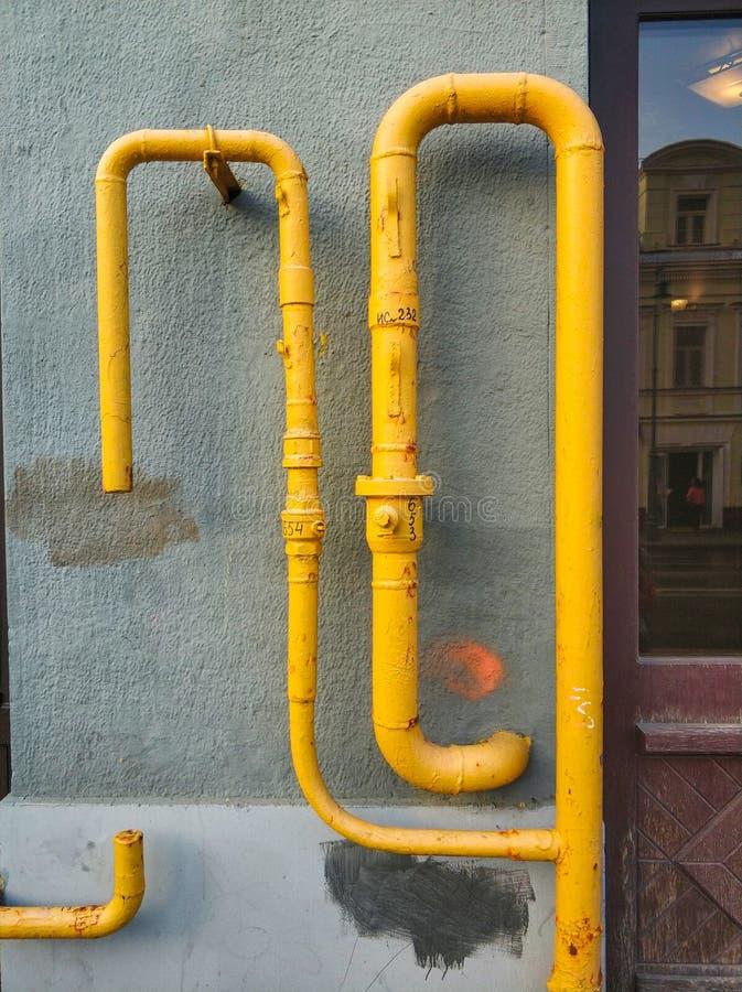 tuyaux jaunes sur le mur d'une maison photos libres de droits