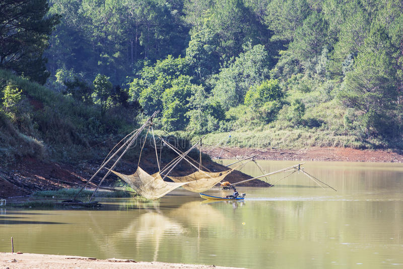 Tuyen Lam lake in the morning. People catch fish with lift net on Tuyen Lam lake in the sunshine, Da Lat city, Lam province, Vietnam. Dalat is famous tourist royalty free stock photos