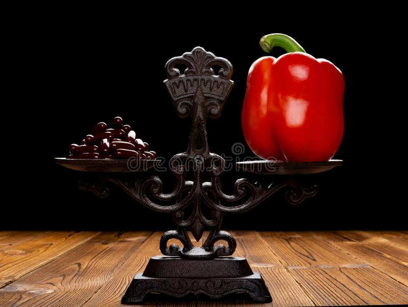 Tuziny czerwony dzwonkowy pieprz na zrównoważonym szalkowym pojęciu zdrowy styl życia, kapsuły i fotografia royalty free