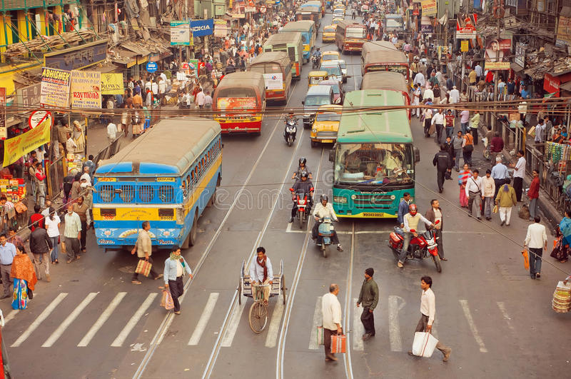 Tvärgata av den upptagna moderna staden i Asien med bilar, cyklar och att gå folk och bussar arkivbild