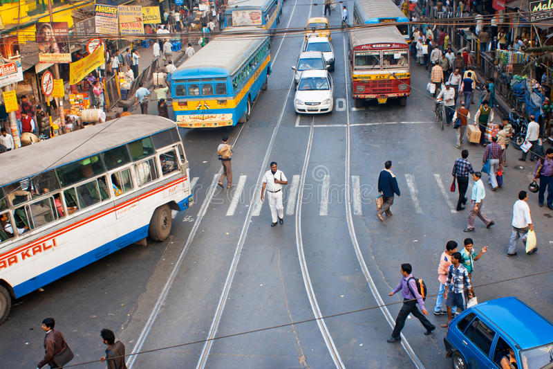 Tvärgata av storstaden med att gå folk och kollektivtrafik arkivbild