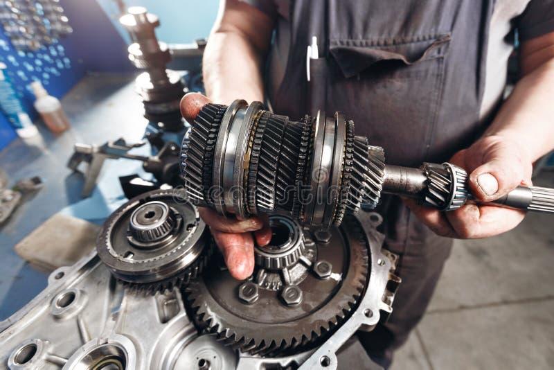 Tvärsnitt av en bilväxellåda mekanikerarbete i garaget handmekaniker i funktionsduglig kläder royaltyfri fotografi