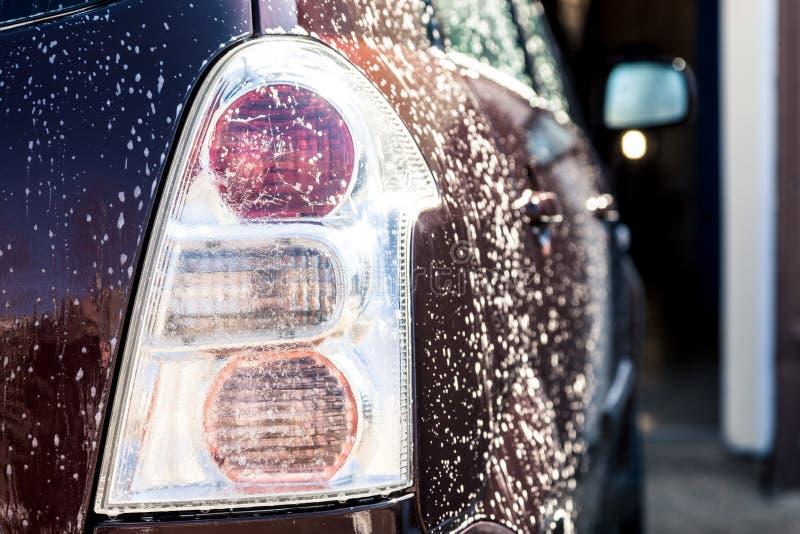 Tvätt av en smutsig bil med skum arkivbild