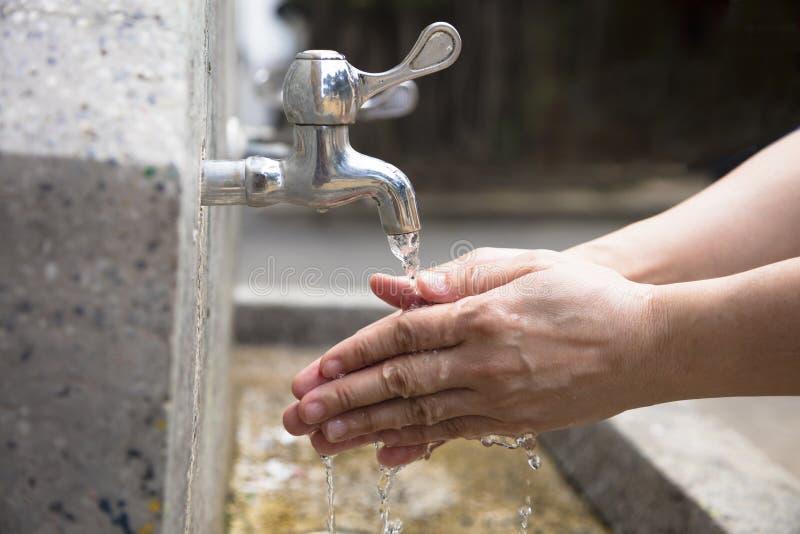 Tvätt av händer under running vatten arkivfoto