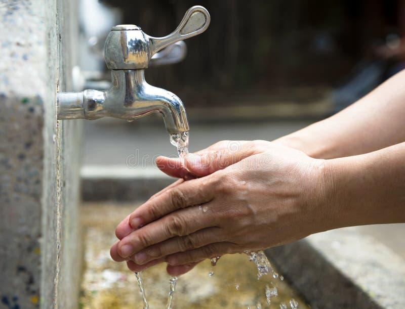 Tvätt av händer under running vatten royaltyfri bild