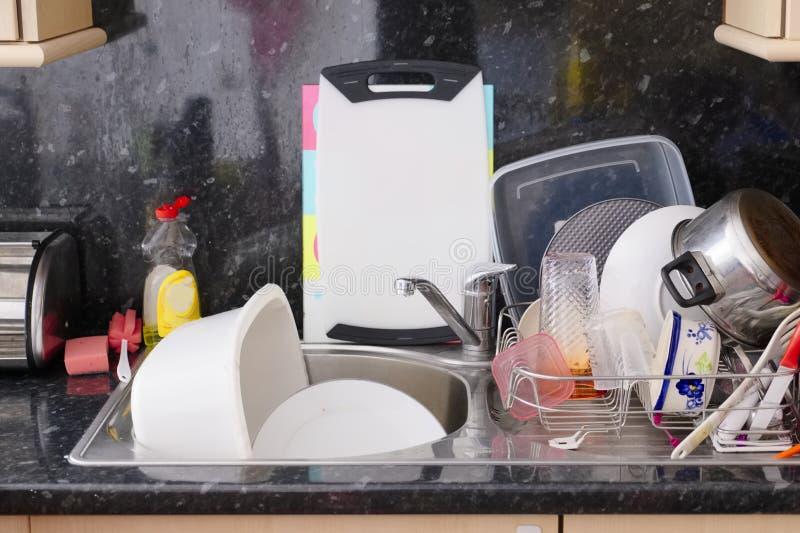 Tvätt upp krukor för bestick för plattor för vaskavloppsrännadisk panorerar slarvigt smutsigt kök arkivbilder