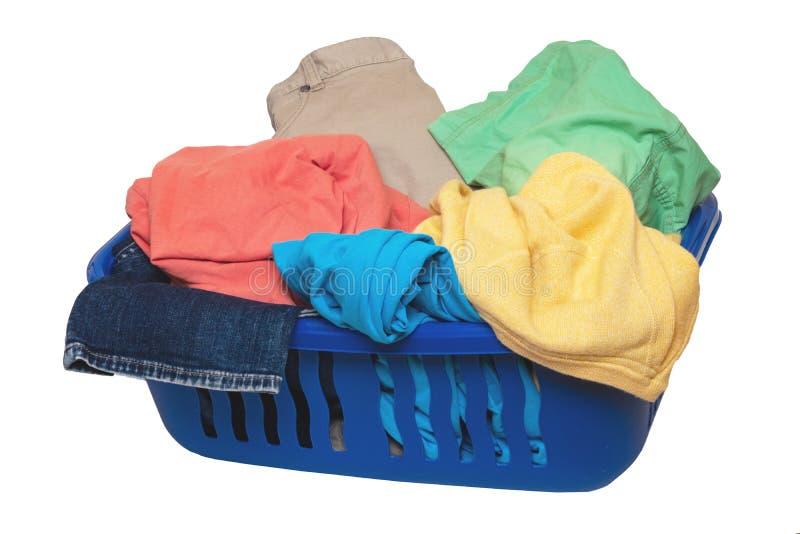 Tvätta den isolerade korgen Closeup av färgrik smutsig kläder i en blå tvättkorg som isoleras på en vit bakgrund arkivfoto