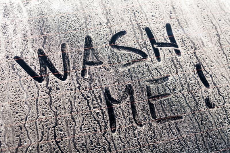 Tvätta mig ord på ett smutsigt bilfönster arkivbild