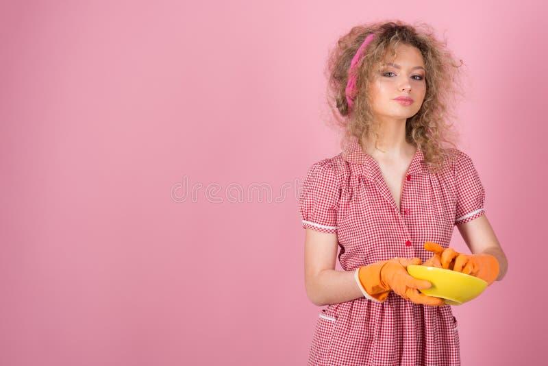 Tvättande disk för hemmafru efter mål Nätt kvinnatvagning i gummihandskar, kopieringsutrymme royaltyfria bilder